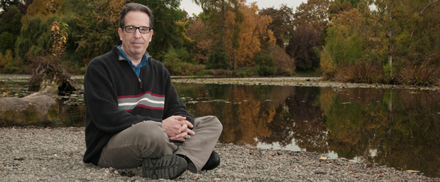 David Levy sitting by a pond